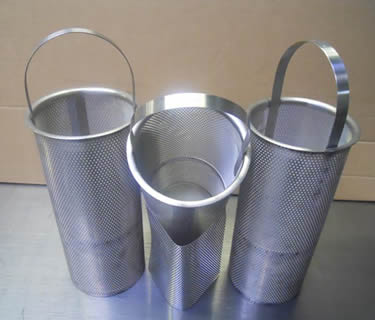 Three stainless steel perforated filter baskets with stainless steel handles on the ground.
